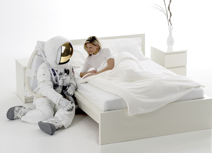Bed with astronaut at the side and woman laying under a sheet. The CoorsTek textile line can keep you cool and comfortable all night long.