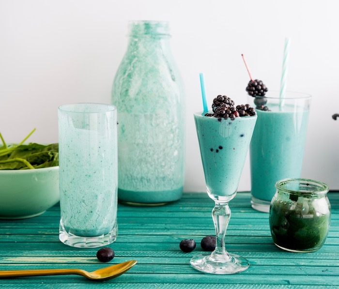 Two blue smoothies, often using spirulina algae for coloring, sitting on a table with an empty drinking glass and a glass bottle.