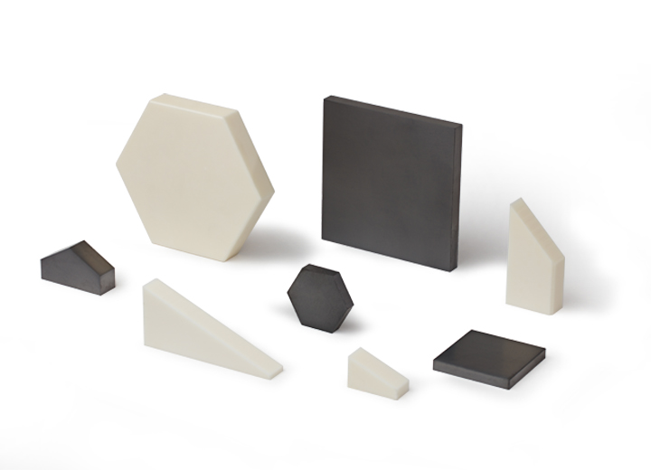 Family of various sizes and shapes of silicon carbide vehicle defense armor tiles.